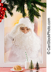 Santa Claus looking inside a home from the other side of the...
