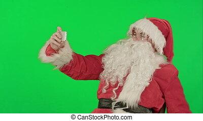 Santa Claus make selfie, holding a big present on a Green Screen Chrome Key
