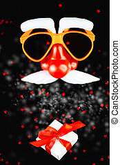 Santa Claus mask and a white gift box with a red ribbon and a scattering of stars on black background