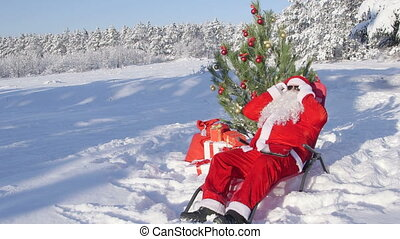 Santa Claus near Christmas tree enjoying frosty sunny day in snow