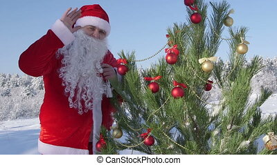 Santa Claus near Christmas tree in snow covered winter forest