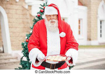 Santa Claus Offering Cookies - Portrait of Santa Claus...