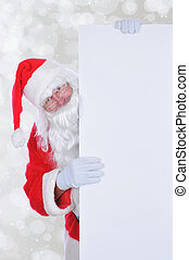 Santa Claus peeking out from behind a large blank sign