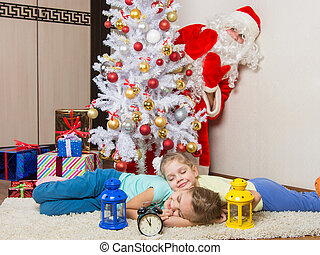 Santa Claus peeking out of a tree in front of which the two...