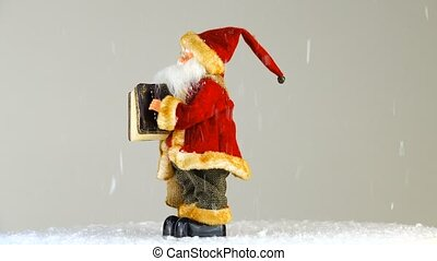 Santa Claus plays a musical instrument on the white screen