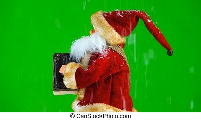 Santa Claus plays a musical instrument on the green screen