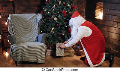 Santa Claus puts a gift under the tree