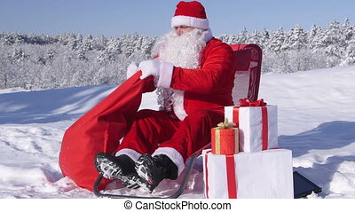 Santa Claus putting Christmas presents in a gift bag on the snow