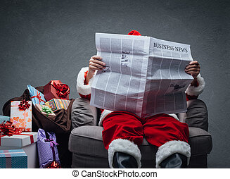 Santa Claus reading business news on a newspaper and...