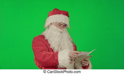 Santa Claus reading letters from children on a Green Screen...