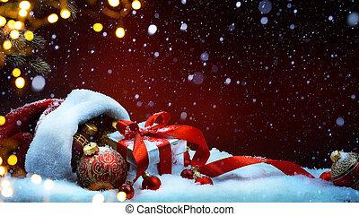 Santa Claus red bag with Christmas balls and gift box on snow