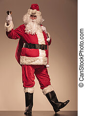 Santa Claus ringing a bell and holding a big bag