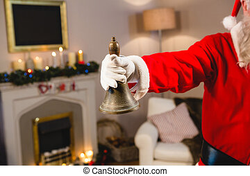 Santa claus ringing a bell at home during christmas time