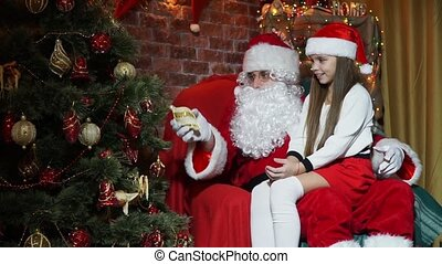 Santa Claus shows a little girl magic toys on the Christmas tree