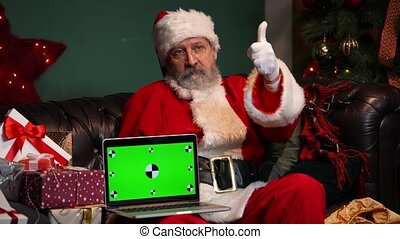 Santa Claus sits on the sofa near decorated Christmas tree and gift boxes, shows notebook with a green screen chrome key while making thumb up gesture. New Years advertising, promotion. E commerce. Close up. Slow motion.