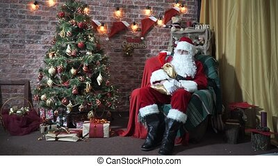 Santa Claus sitting in a chair near a Christmas tree meets children. Slow motion