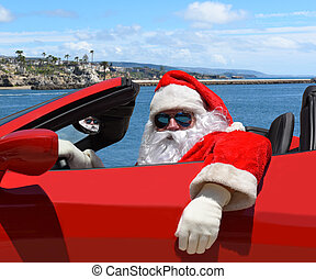 Santa Claus sitting in his red sports car at the beach