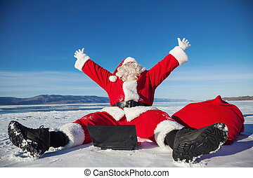 Santa Claus sitting on snow glad news in the laptop, shooting was conducted in a sunny day on lake Baikal