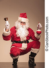 Santa CLaus sitting with a bell in his left hand