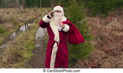 Santa Claus talking on phone in forest