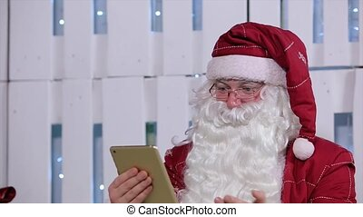 Santa Claus Use Digital Tablet in Room with Christmas Tree and Gifts