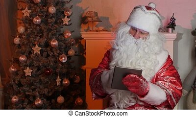 Santa Claus using tablet computer to surf internet and communicate in social media with children