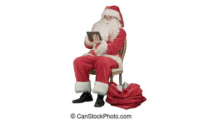 Santa Claus using tablet computer to surf internet and communicate in social media with children on white background