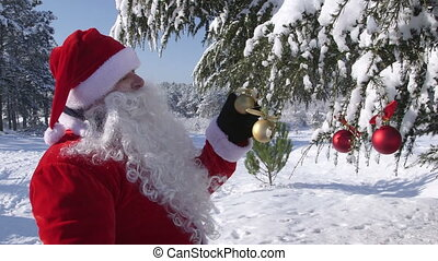 Santa Claus waving hand near decorated Christmas tree in winter forest