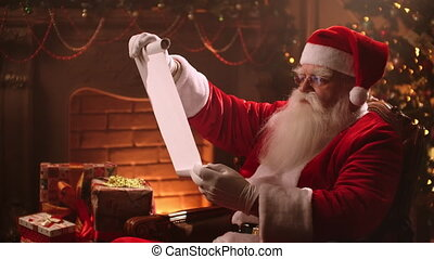 Santa Claus with a beard and a suit sits on a chair and reads a scroll with a list of children for gifts.