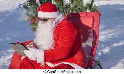 Santa Claus with gift bag using tablet computer in snow covered winter forest