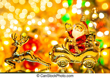 Santa Claus with gifts on car with christmas deer, on bokeh background