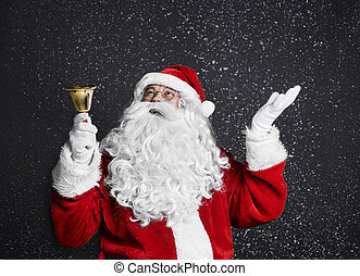 Santa claus with handbell among snow falling