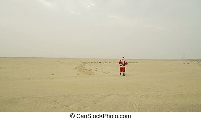 Santa claus with sack of presents is coming to town from the desert. Santa walks on sand in desert, found asphalt road, looking for a city