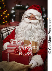 Santa Claus with stack of christmas presents