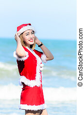 Santa claus woman on the beach.