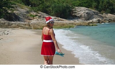 Santa Claus woman walking on the beach near the sea in slow motion. Christmas and new year vacation on Koh Samui, Thailand. 1920x1080