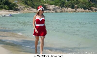 Santa Claus woman walking on the beach near the sea in slow motion. Christmas and new year vacation on Koh Samui, Thailand.