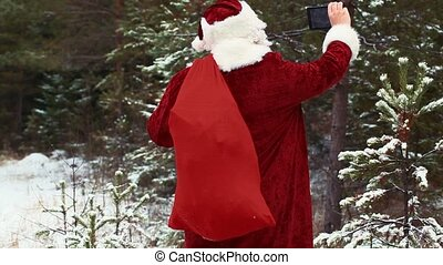 Santa Clause filmed with tablet PC in the snowy woods