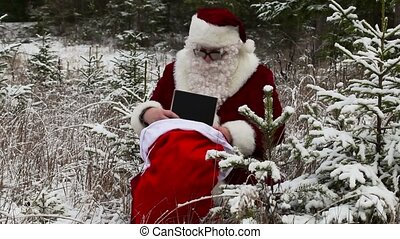 Santa Clause with gift box and gift bag in the snowy woods