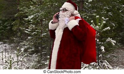 Santa Clause with smartphone in the forest