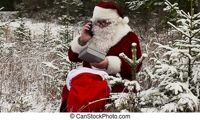 Santa Clause with smartphone near gift bag in the snowy...