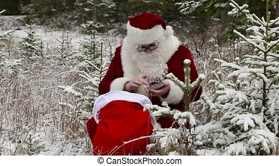 Santa Clause with tablet PC near gift bag in the snowy woods