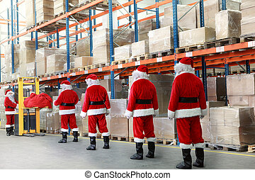 santa clauses in line in warehouse