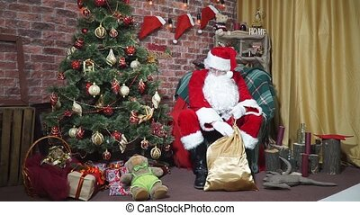 Santa collecting gifts in a bag sitting in a chair at the Christmas tree