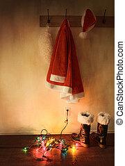 Santa costume hanging on coat hook with christmas lights