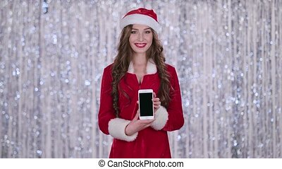 Santa girl holds the phone in her hands and looks into the distance. Bokeh background