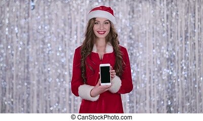 Santa girl holds the phone in her hands and looks into the distance. Bokeh background. Slow motion