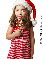 Santa girl licking Christmas tree lollipop candy - A...