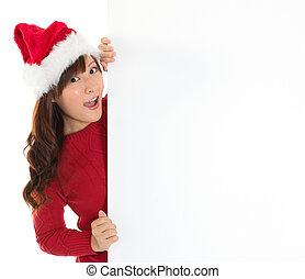Santa girl peeking from behind blank sign billboard.