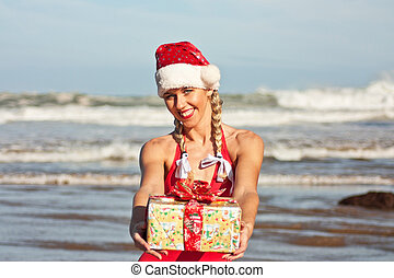 Santa girl with gift on the beach